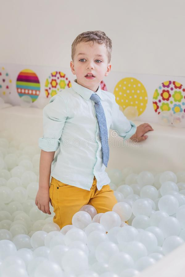 Cute boy in the children`s playroom plays royalty free stock photo