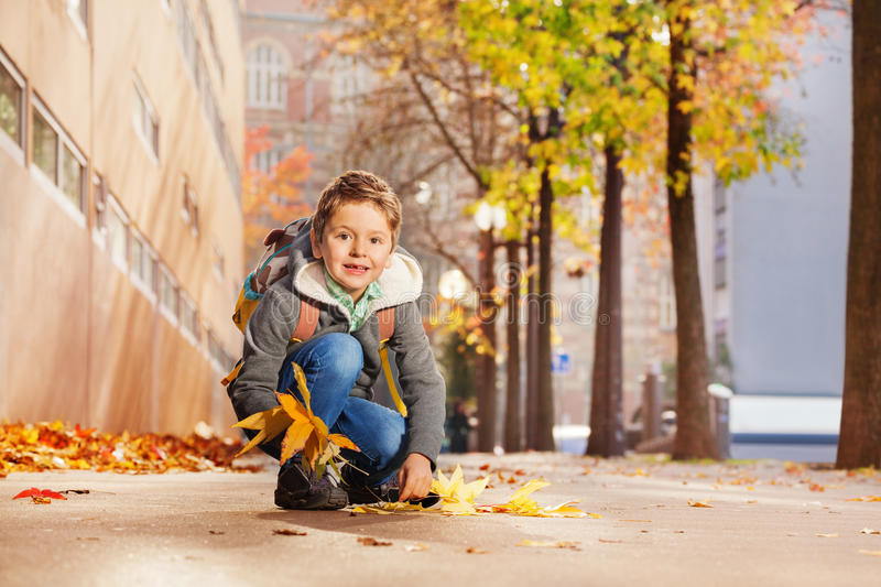 Cute boy collecting maple leaves on his way home. Cute schoolboy collecting maple leaves walking along the autumn street on his way home stock image