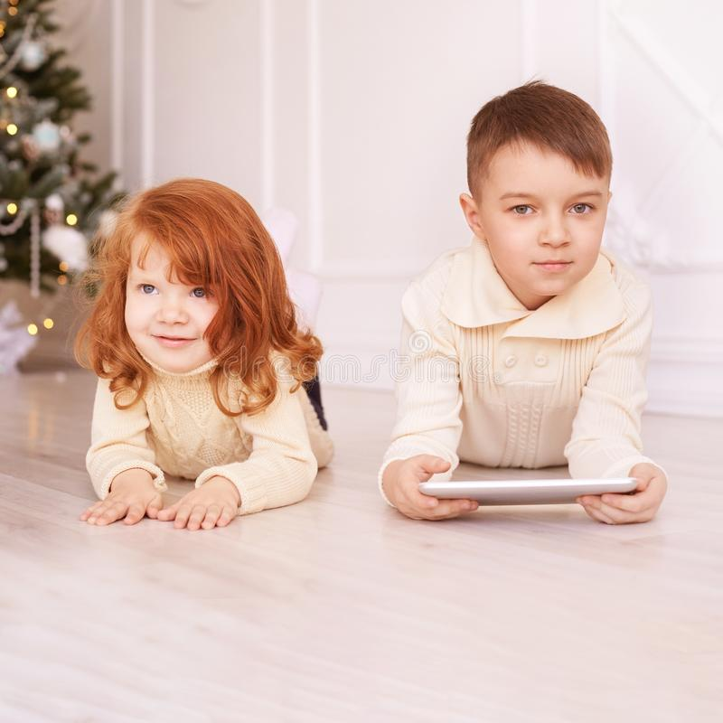 Cute boy. Computer tablet. play game, chat. Training. light interior. Brother and sister stock photos