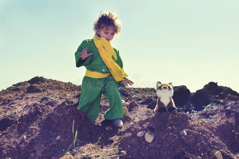 Cute boy with curly blond hair playing with plush fox toy above pile of earth wearing green clothes and yellow scarf. Selective focus royalty free stock images