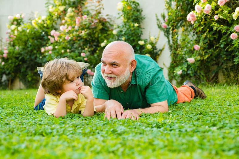 Cute boy with dad playing outdoor. Child with Grandfather dreams in summer in nature. Happy family Grandson hugs his. Grandpa on holiday. Happy grandfather and royalty free stock image