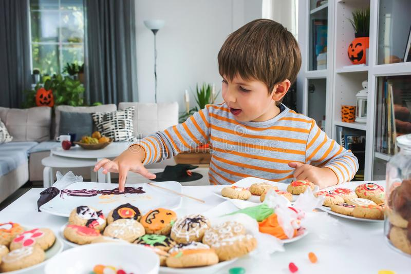 Cute boy decorating cookies for Halloween stock photo