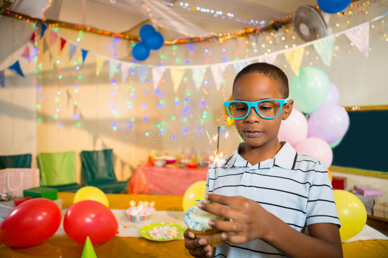 Cute boy decorating cupcake with sparkler during birthday party. At home stock photo