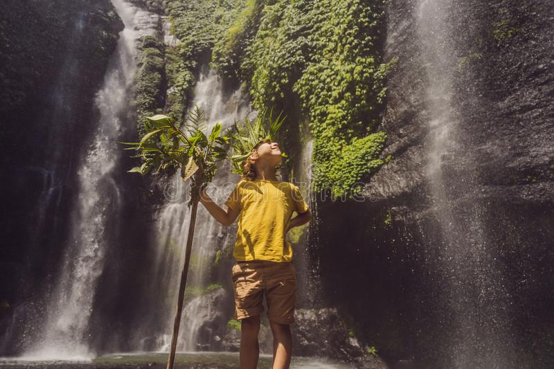Cute boy depicts the king of the jungle against the backdrop of a waterfall. Childhood without gadgets concept. Traveling with children concept. Childhood royalty free stock image