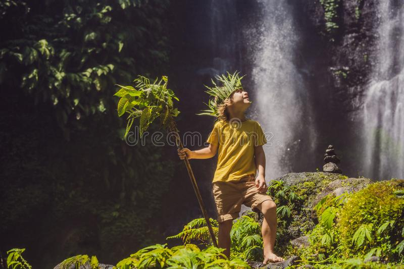 Cute boy depicts the king of the jungle against the backdrop of a waterfall. Childhood without gadgets concept. Traveling with children concept. Childhood stock photos