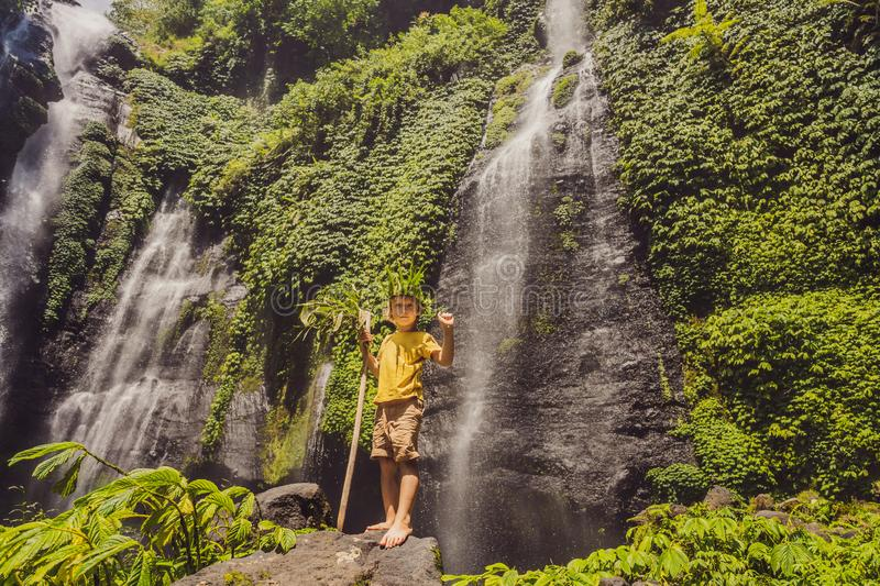 Cute boy depicts the king of the jungle against the backdrop of a waterfall. Childhood without gadgets concept. Traveling with children concept. Childhood stock photography