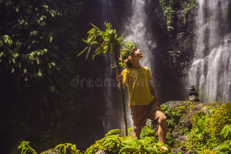 Cute boy depicts the king of the jungle against the backdrop of a waterfall. Childhood without gadgets concept. Traveling with children concept. Childhood royalty free stock photo