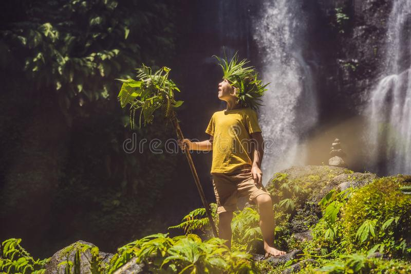 Cute boy depicts the king of the jungle against the backdrop of a waterfall. Childhood without gadgets concept. Traveling with children concept. Childhood stock photo