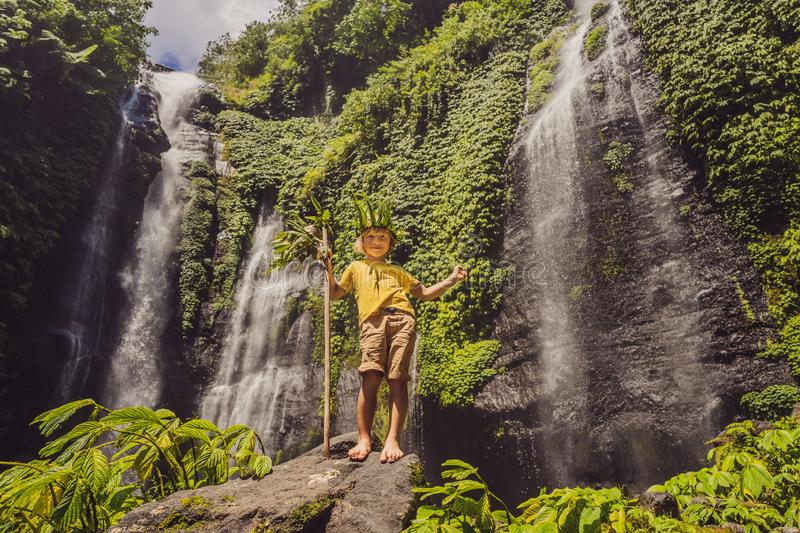 Cute boy depicts the king of the jungle against the backdrop of a waterfall. Childhood without gadgets concept. Traveling with children concept. Childhood stock images