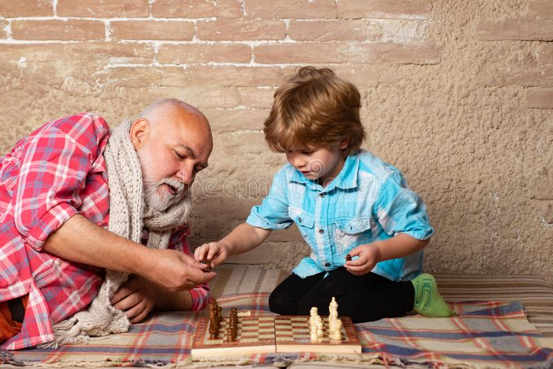 Cute boy developing chess strategy. Senior man thinking about his next move in a game of chess. Chess competition. Senior man teaching his grandson to play royalty free stock image