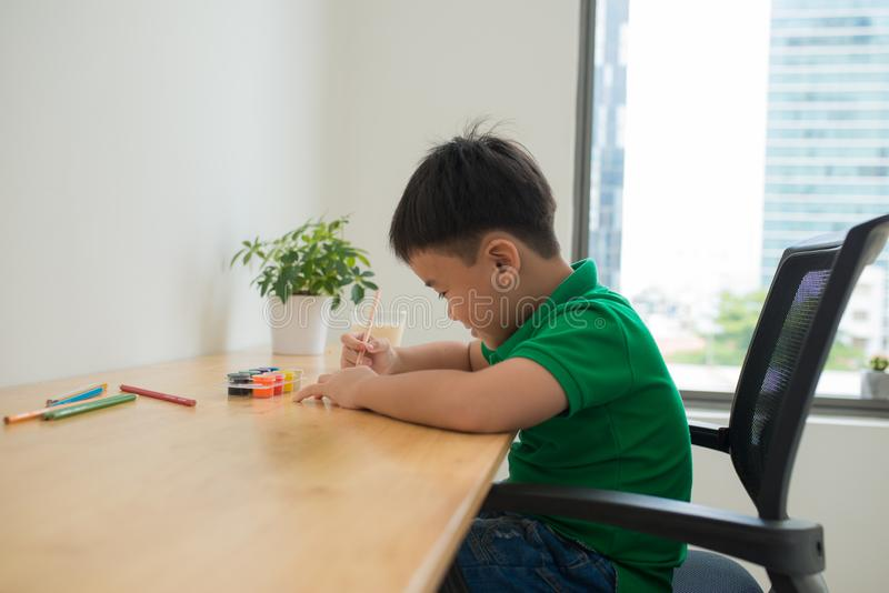 Cute boy doing homework, coloring pages, writing and painting. Children paint. Kids draw. Preschooler with books at home. stock photos