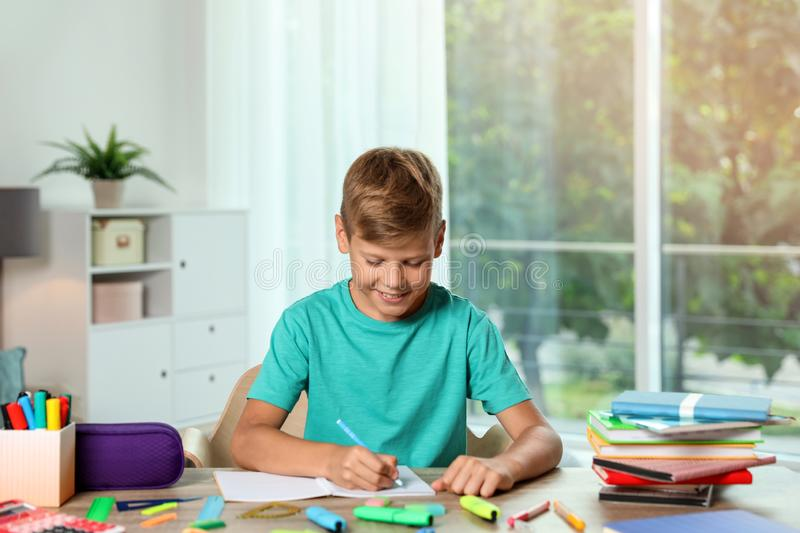 Cute boy doing homework at table with school stationery. Indoors stock photo
