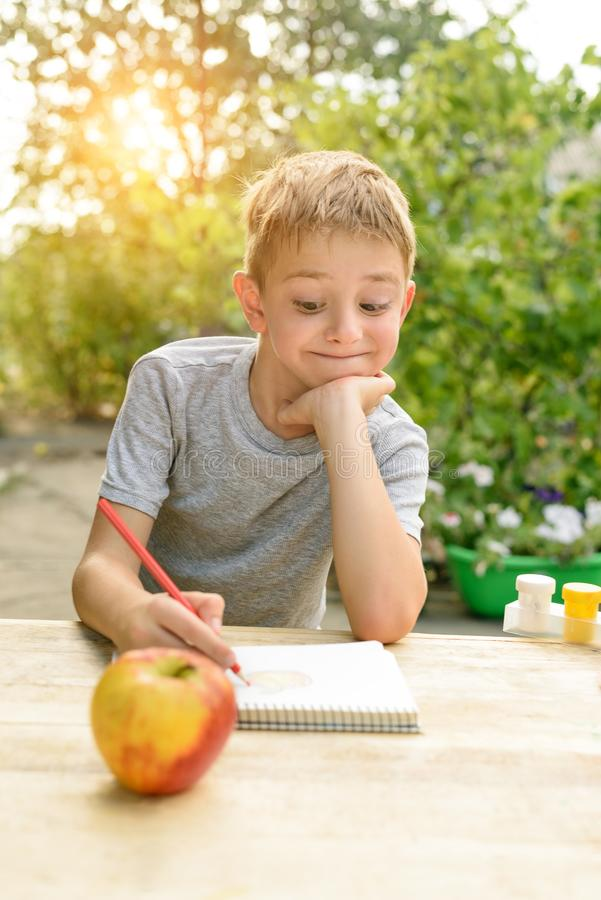 Cute boy draws with pencils still life. Open air. Garden in the background. Creative concept.  stock photography