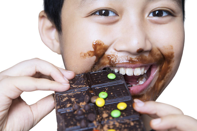 Cute boy eating chocolate on studio stock image