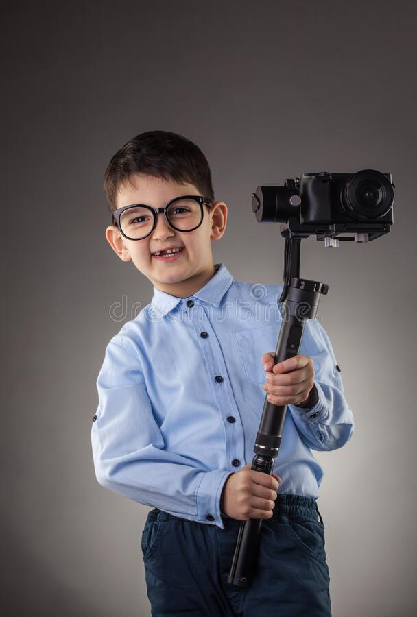 Cute boy with electronic steadicam on the gray background royalty free stock images