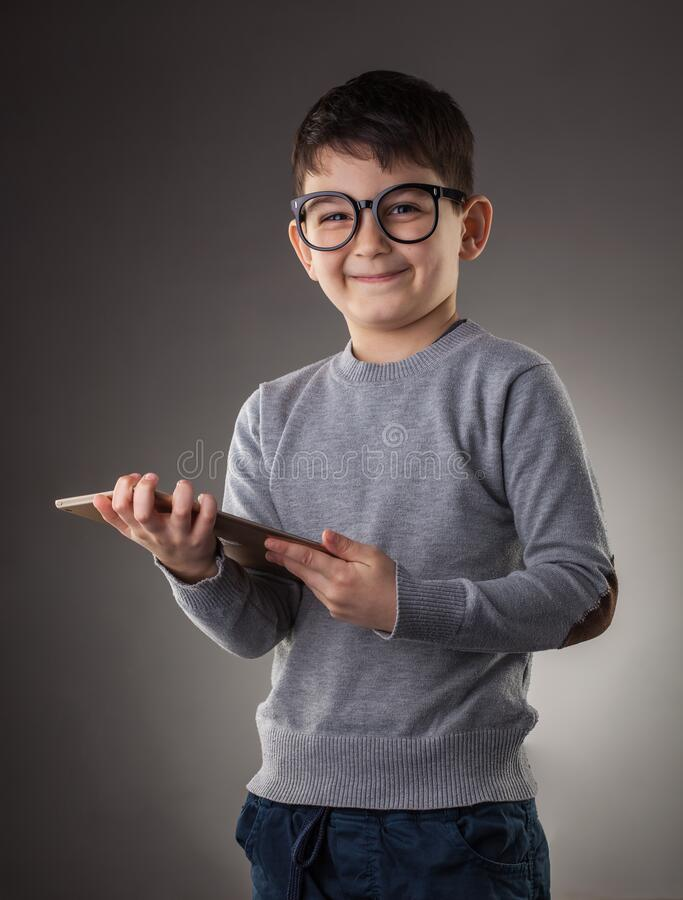 Cute boy with electronic tablet on the gray background stock photo