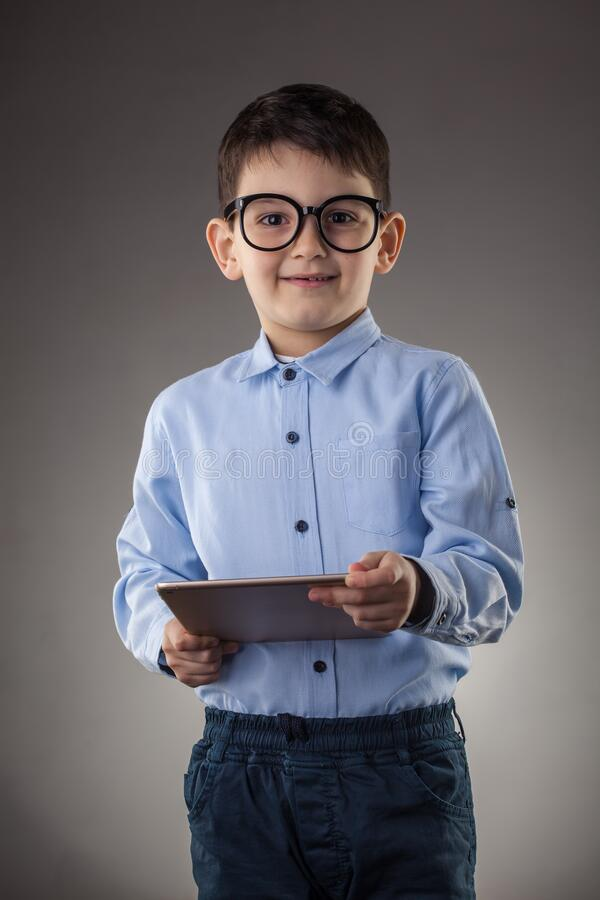 Cute boy with electronic tablet on the gray background stock images