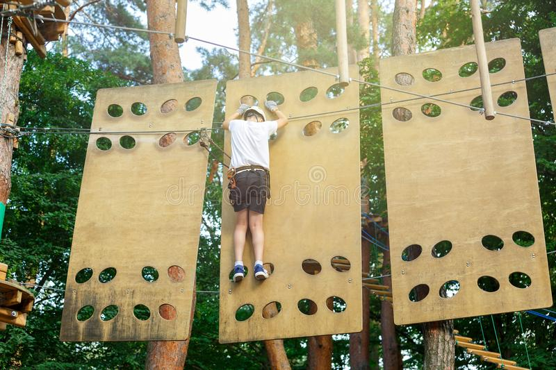 Cute boy enjoying activity in climbing adventure park at sunny summer day. Kid climbing in rope playground structure. Safe. Climbing with helmet insurance royalty free stock photos