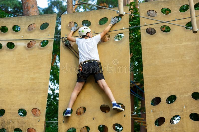Cute boy enjoying activity in climbing adventure park at sunny summer day. Kid climbing in rope playground structure. Safe. Climbing with helmet insurance royalty free stock photography