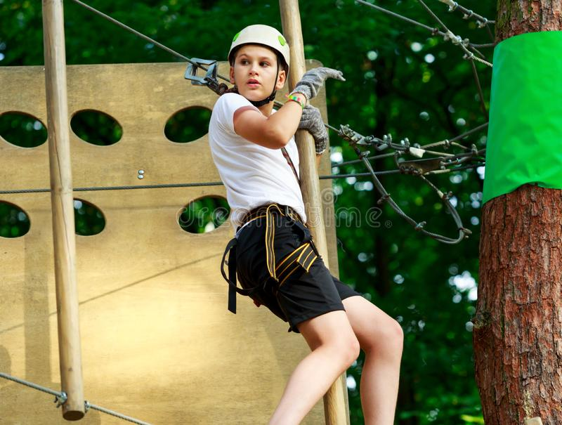 Cute boy enjoying activity in climbing adventure park at sunny summer day. Kid climbing in rope playground structure. Safe. Climbing with helmet insurance royalty free stock image