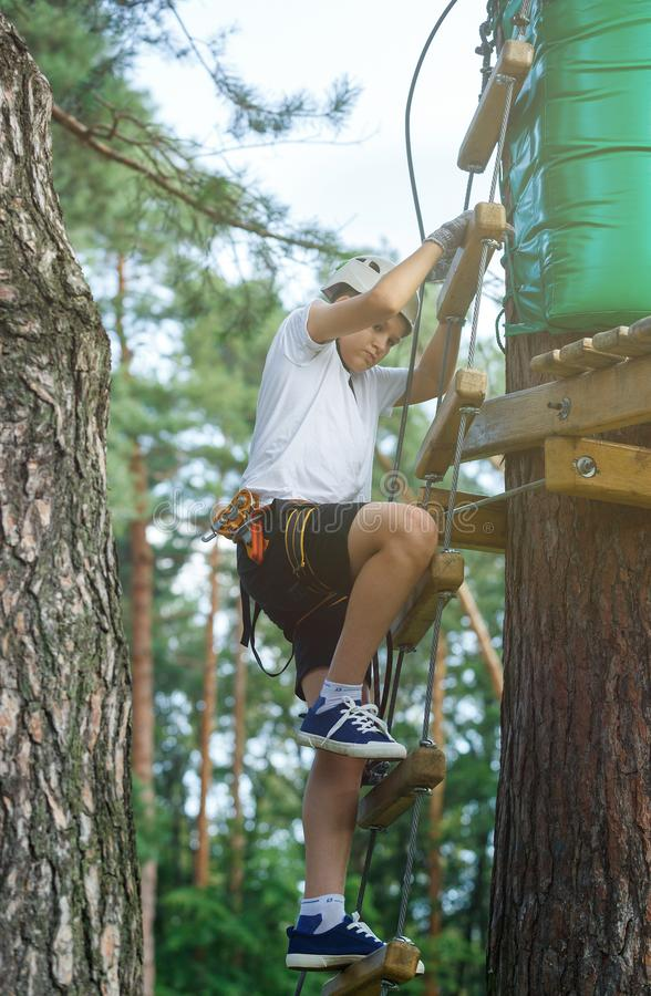 Cute boy enjoying activity in climbing adventure park at sunny summer day. Kid climbing in rope playground structure. Safe. Climbing with helmet insurance stock images