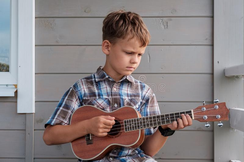Cute boy of European appearance plays the ukulele royalty free stock photos