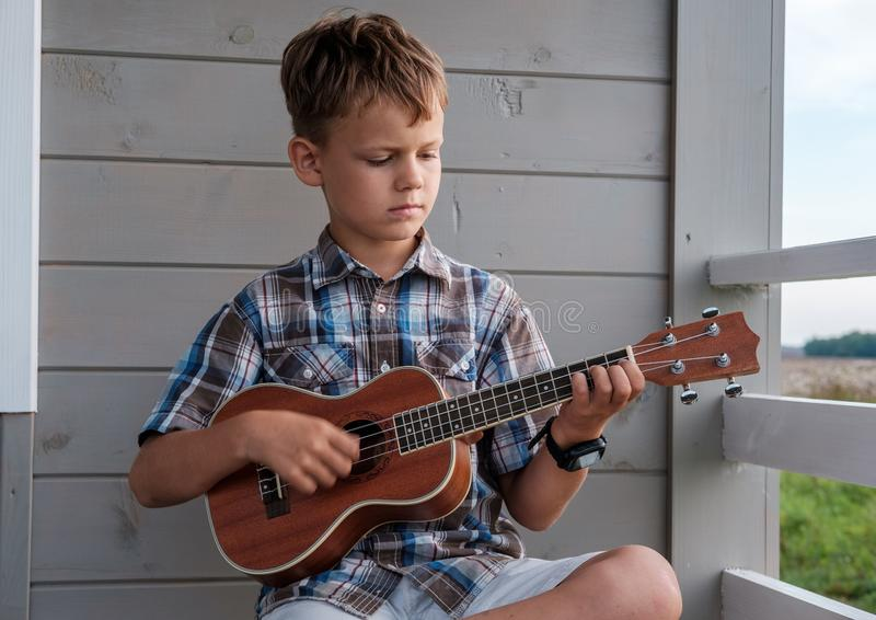 Cute boy of European appearance plays the ukulele stock photo