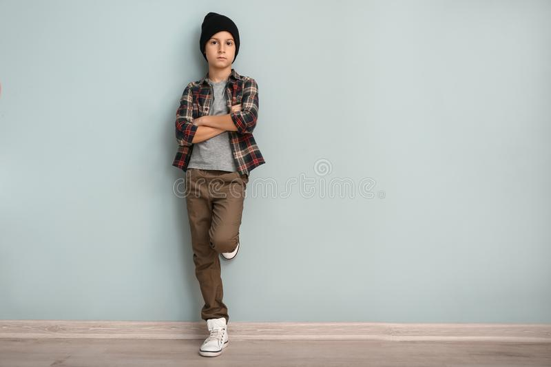 Cute boy in fashionable clothes near color wall stock photography