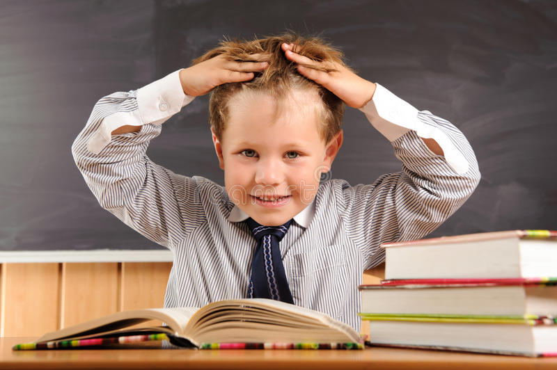 Cute boy fooling at the lesson. Cute elementary aged boy fooling at the lesson royalty free stock images