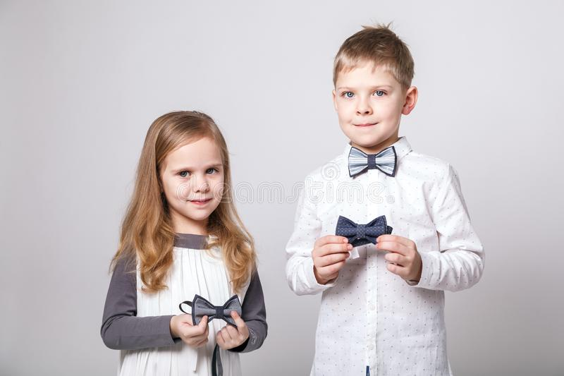 Cute boy and girl in fashionable clothes with bow tie posing on gray background. Concept of children style and fashion royalty free stock photos