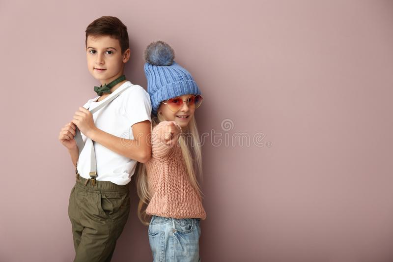 Cute boy and girl in fashionable clothes on color background stock photography