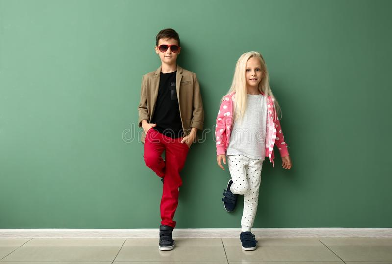 Cute boy and girl in fashionable clothes near color wall royalty free stock photos