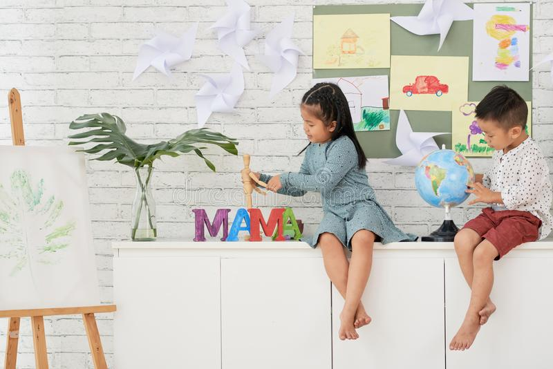 Boy and girl playing in art class stock photography