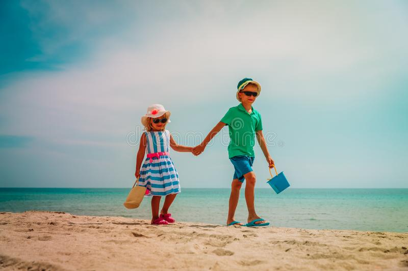 Cute boy and girl walk on tropical beach vacation royalty free stock images