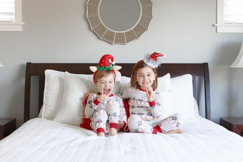 Boy and girl on bed with Christmas pajamas royalty free stock photography