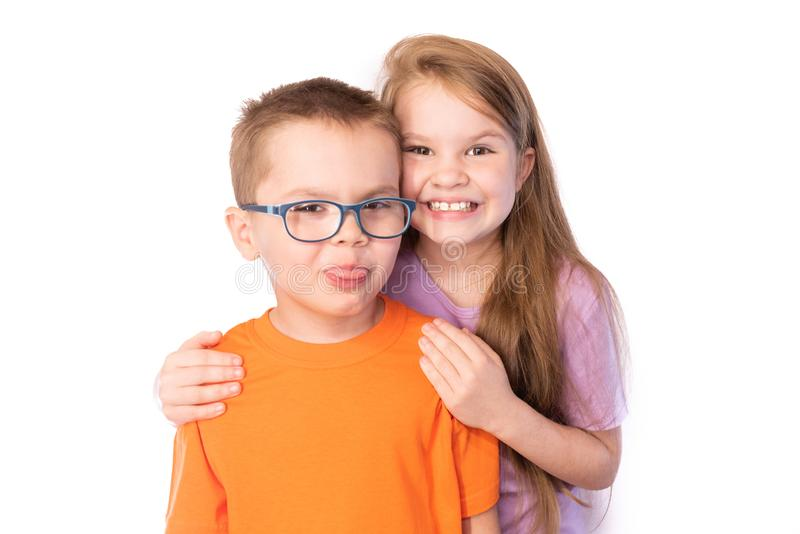 Cute boy in glasses showing tongue, and the little girl,smiling and hugging his shoulders, isolated on white background stock images