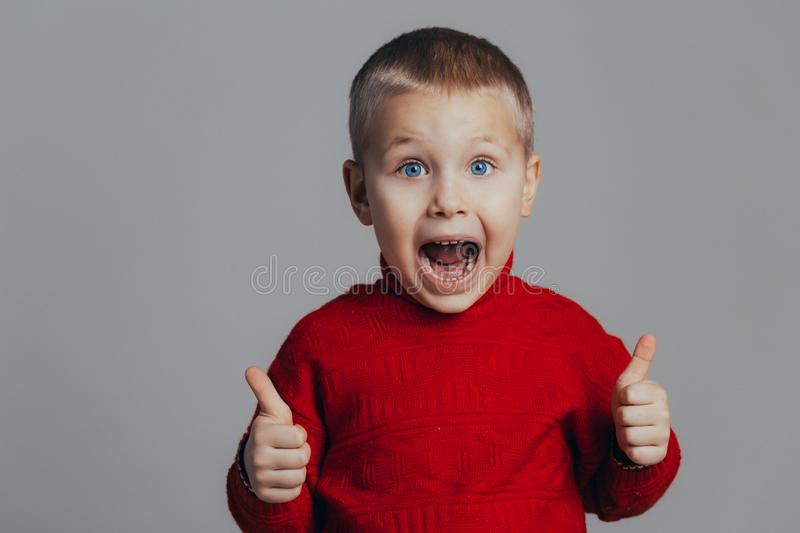 Cute boy on a gray background raised his finger up and says ok and open mouth royalty free stock photo