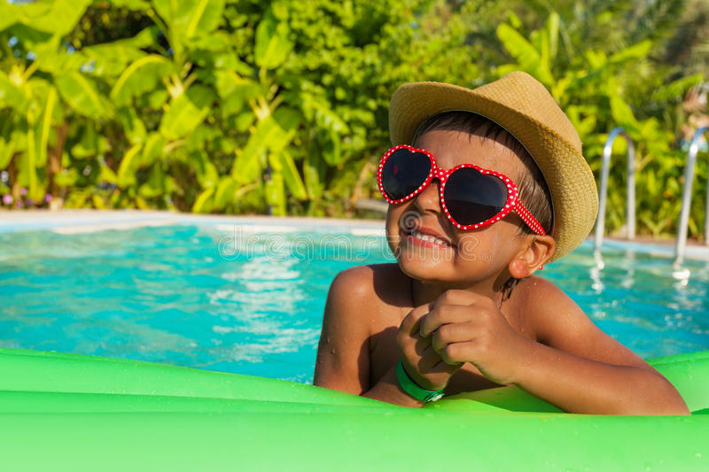 Cute boy on green airbed in the swimming pool. Cute boy in heart-shaped sunglasses on green airbed in the swimming pool outside in summer stock images