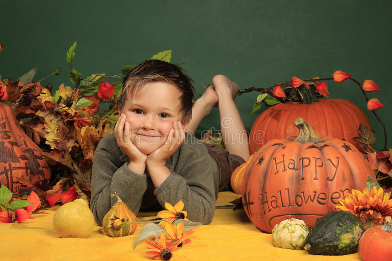 Cute boy and halloween pumpkins royalty free stock images