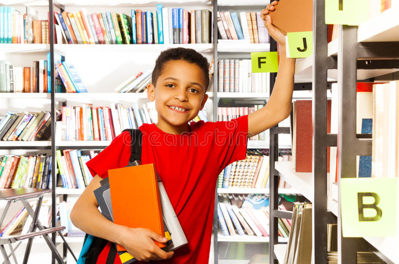 Cute boy with hand on bookshelf holds many books royalty free stock image