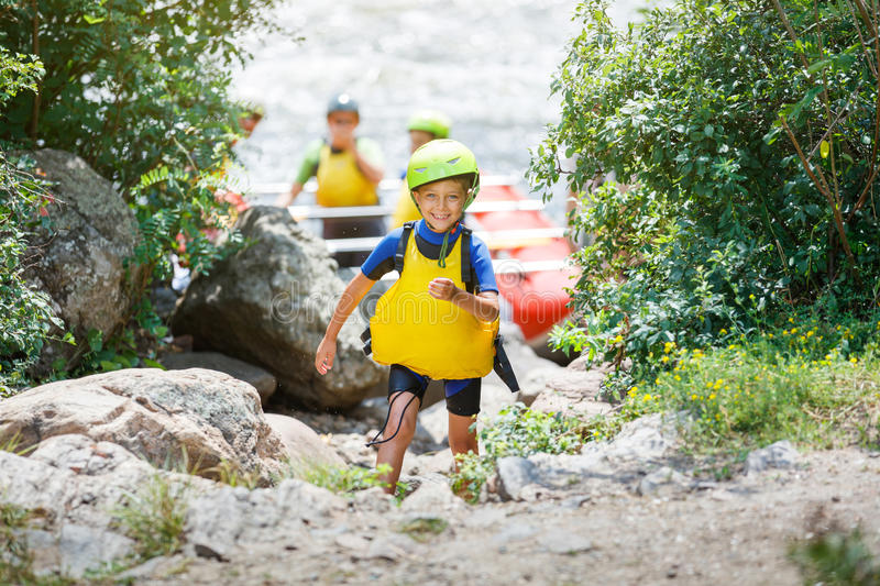 Cute boy in helmet and live vest ready for rafting on the catamaran. With his family stock photography
