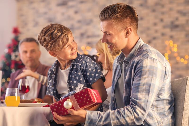 Cute boy and his father with Christmas gift at home royalty free stock image
