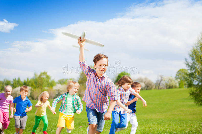 Cute boy and his friends run with big airplane toy royalty free stock photo