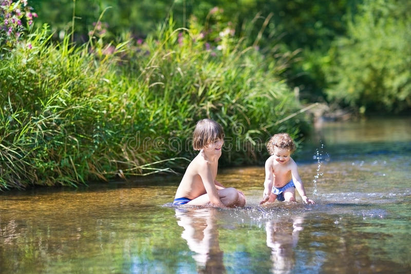 Cute boy and his little baby sister in the water in lake royalty free stock photography