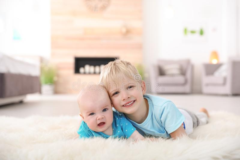 Cute boy with his little sister lying on fur rug royalty free stock photo