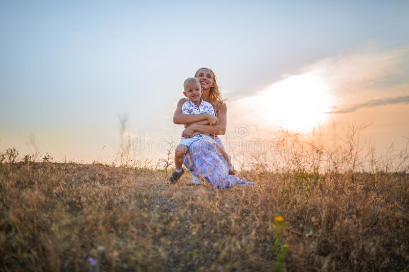 A cute boy and his mother on a sky background. A happy family together enjoying a beautiful nature. Copy space. stock photography