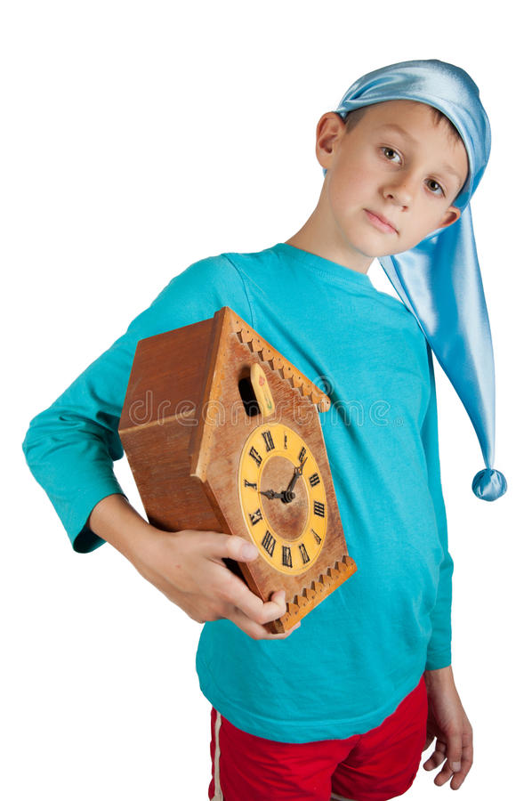 Cute boy holding clock isolated on white. Cute boy in blue pajamas and sleeping hat holding clock isolated on white royalty free stock photos