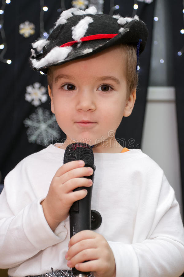 Cute boy holding microphone on stage, dressed as a snowman royalty free stock photos