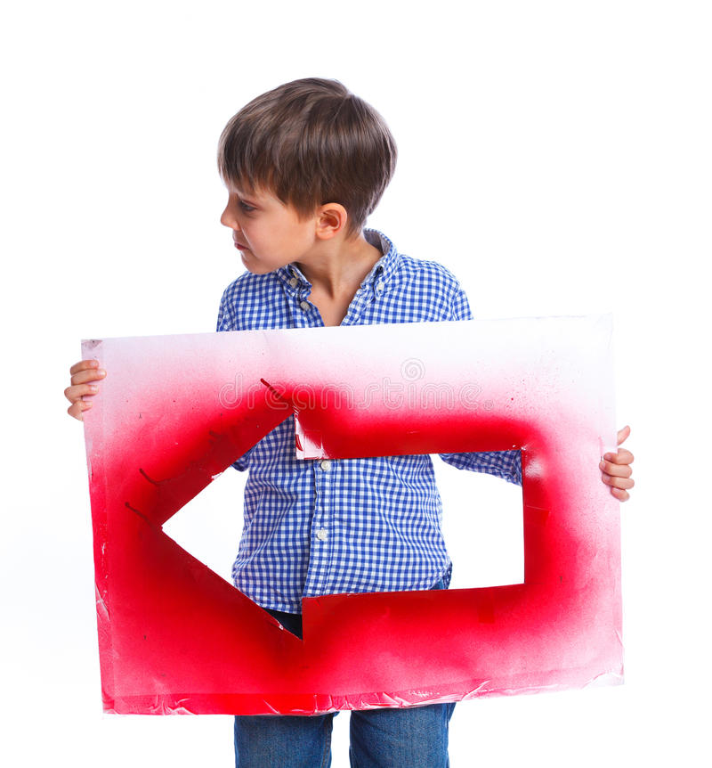 Cute boy holding red arrow. Portrait of cute boy holding red arrow. Isolated on white background royalty free stock photography