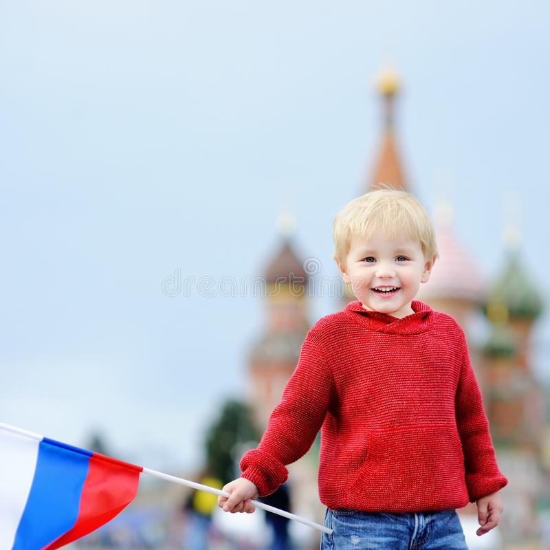 Cute boy holding russian flag with and Vasilevsky descent on background. Cute toddler boy holding russian flag with Red Square and Vasilevsky descent on royalty free stock photo
